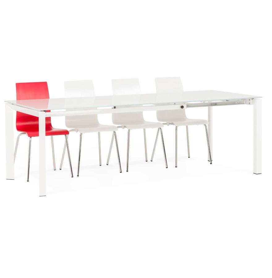 Table blanche avec un plateau en verre et des pieds en métal.